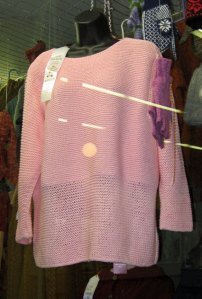 Pink sweater with ribbon hanging in state fair display case