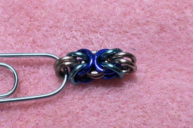 Byzantine weave chain maille attached to a paper clip.