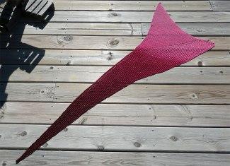 Bandwagon shawlette lying flat on the ground.
