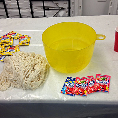 Yarn, a large plastic bowl, and several packets of Kool-Aid.