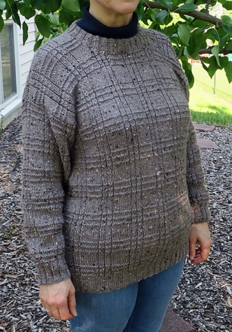 Gray sweater with a textural plaid design knitted into it.