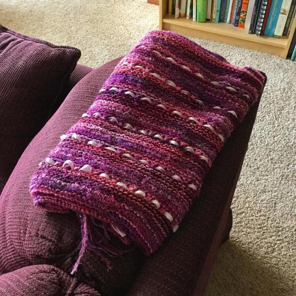 Purple and pink wrap folded and lying on the back of a couch.
