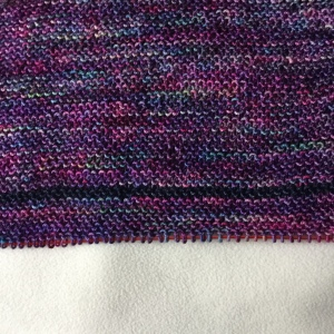 Close-up of purple shawl with blue stripe, on a knitting needle.