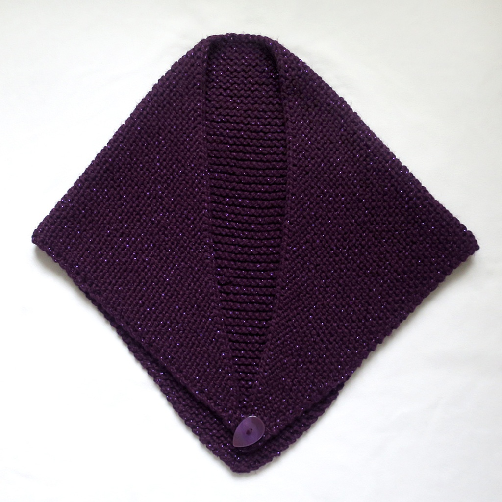 A knitted purple shawl with a purple button.