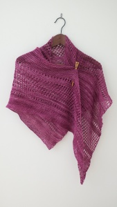 Rose Ardent shawlette draped on a hanger.