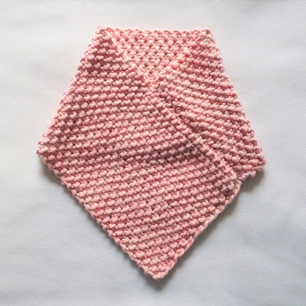 Pink knitted cowl in seed stitch.